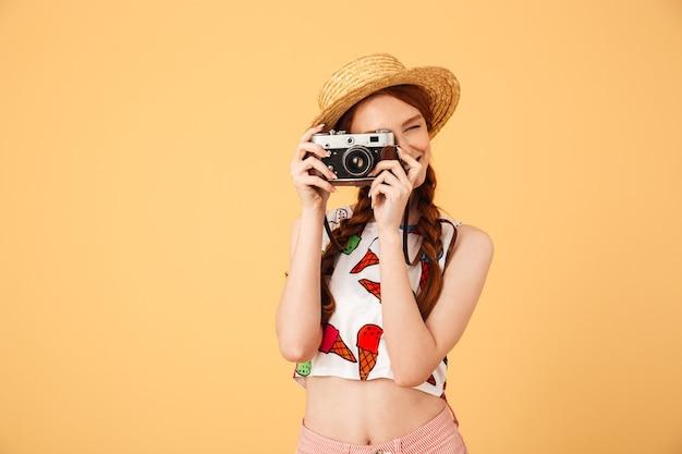 Afbeelding van een jonge mooie roodharige vrouw fotograaf toerist gekleed in ijs bedrukt t-shirt poseren geïsoleerd over gele muur met camera.