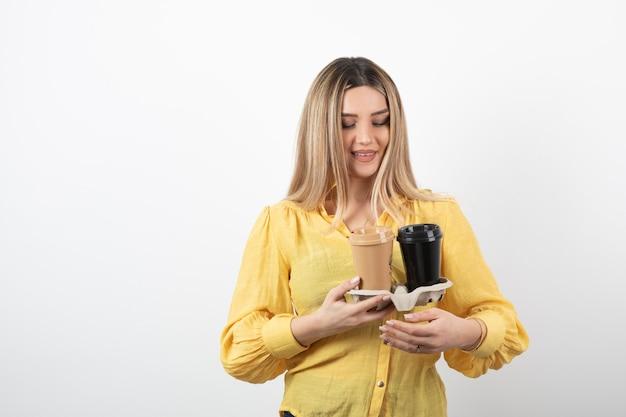 Afbeelding van een jonge persoon die kopjes koffie op wit kijkt.