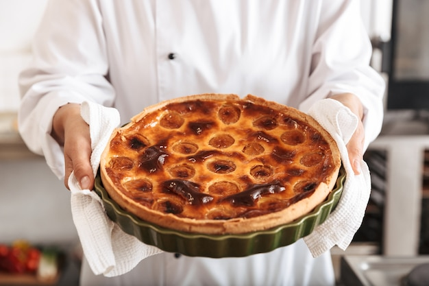 Afbeelding van een jonge vrouw chef-kok dragen witte uniforme appeltaart houden, tijdens het koken in de keuken bij de bakkerij