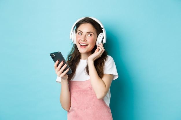 Afbeelding van een jonge vrouw die een koptelefoon op zet en muziek kiest op smartphone, telefoon vasthoudt, liedje luistert, over blauwe achtergrond staat