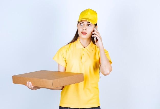 Afbeelding van een jonge vrouw die een pakket vasthoudt en via een mobiele telefoon over een witte muur praat.