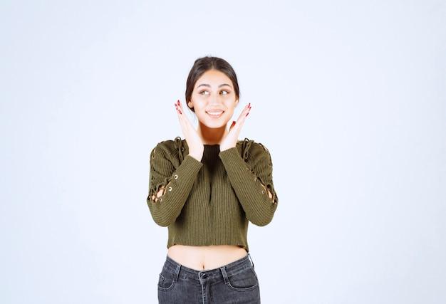 Afbeelding van een jonge vrouw die gelukkig poseert terwijl ze op een witte achtergrond staat.
