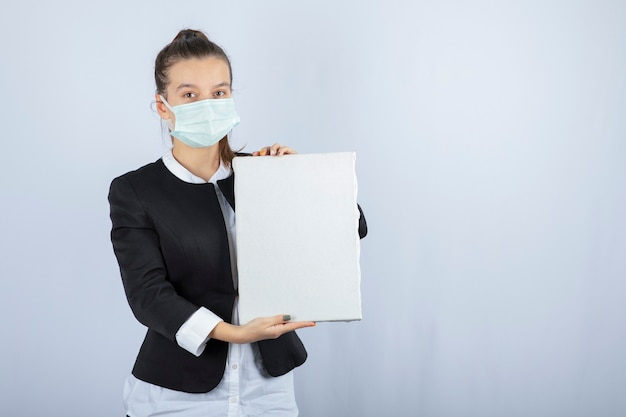Afbeelding van een jonge vrouw die in gezichtsmasker leeg canvas over witte muur houdt. hoge kwaliteit foto
