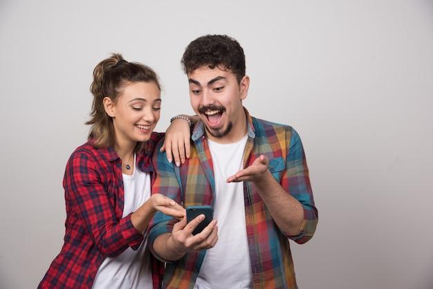 Afbeelding van een jonge vrouw die naar de mobiele telefoon van haar man kijkt.