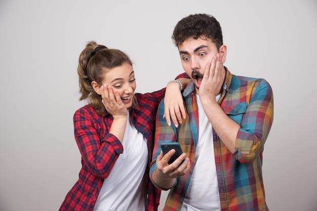 Afbeelding van een jonge vrouw die naar de mobiele telefoon van haar man kijkt. Gratis Foto