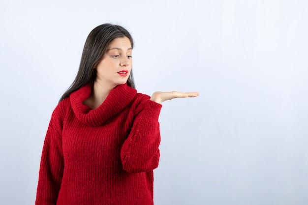 Afbeelding van een jonge vrouw in een rode trui die hand op een witte achtergrond toont