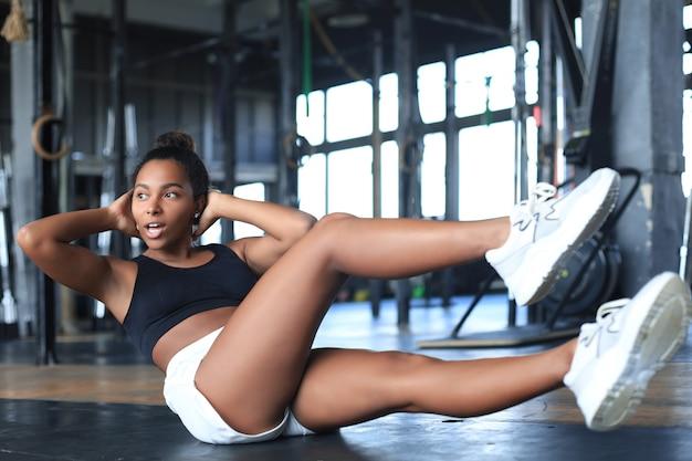 Afbeelding van een jonge vrouw in sportkleding die crunches doet in de sportschool.