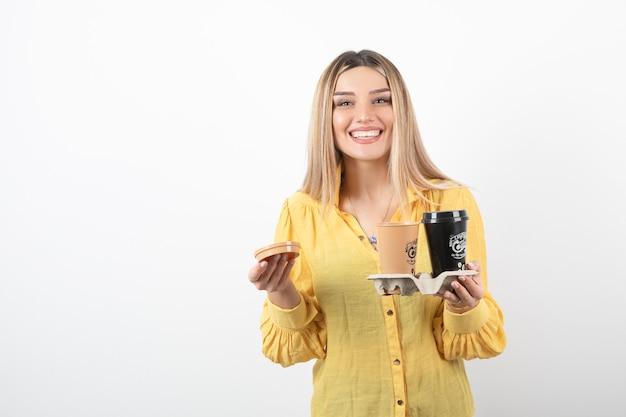 Afbeelding van een jonge vrouw met kopjes koffie tijdens het glimlachen.