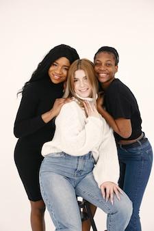 Afbeelding van een jonge vrouw. multiraciale vrienden poseren geïsoleerd op witte muur achtergrond.