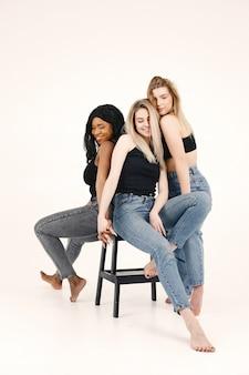 Afbeelding van een jonge vrouw. multiraciale vrienden poseren geïsoleerd op witte muur achtergrond. Gratis Foto