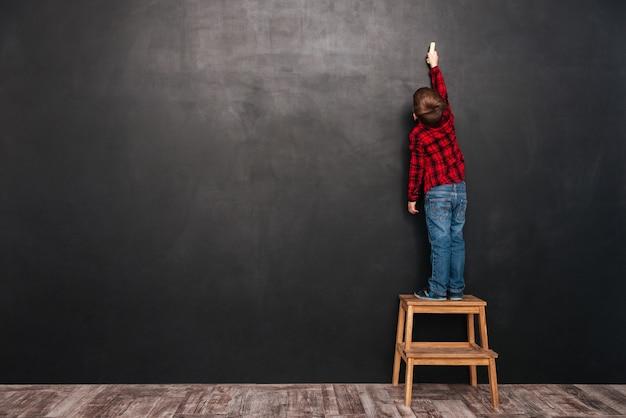 Afbeelding van een klein kind dat op een krukje bij het bord staat en erop tekent