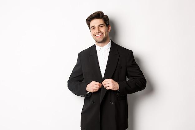 Afbeelding van een knappe en zelfverzekerde zakenman met baard, button-down jas en glimlachend, staande tegen een witte achtergrond