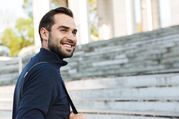 Afbeelding van een knappe gelukkige jonge sterke sportman die buiten op de locatie van het natuurpark poseert.