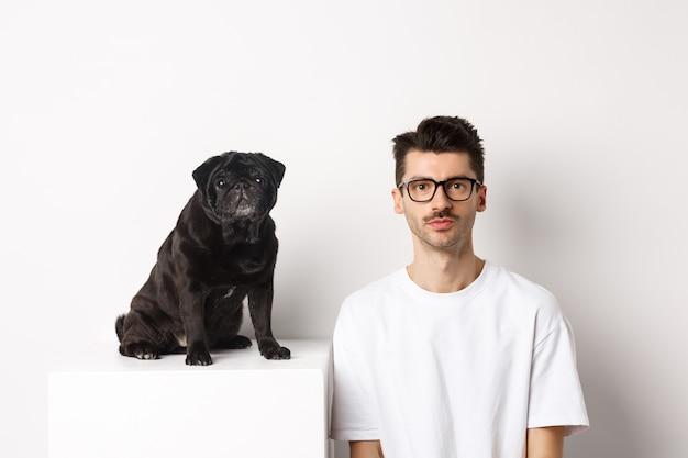 Afbeelding van een knappe hipster in een bril die naast een zwarte schattige mopshond zit, beide staren naar de camera op een witte achtergrond.