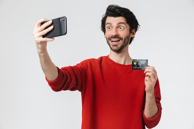 Afbeelding van een knappe jonge opgewonden man die zich voordeed op een witte muur, neem een selfie door de mobiele telefoon met creditcard.