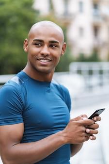 Afbeelding van een knappe jonge, sterke sportman die buiten met een mobiele telefoon aan het chatten is.