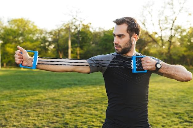Afbeelding van een knappe jonge sterke sportman die buiten op de locatie van het natuurpark poseert, maakt oefeningen met fitnessapparatuur.