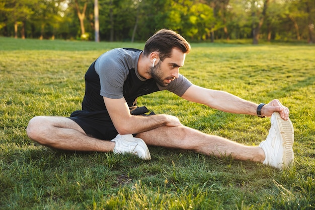 Afbeelding van een knappe jonge sterke sportman die buiten op de locatie van het natuurpark poseert, maakt rekoefeningen die muziek luisteren met oortelefoons.