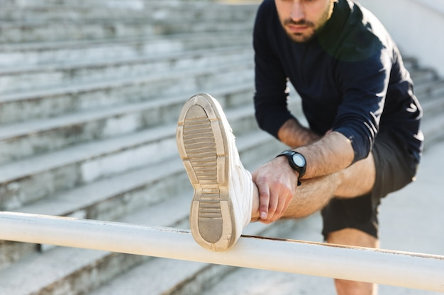 Afbeelding van een knappe jonge sterke sportman die buiten op de locatie van het natuurpark poseert, maakt rekoefeningen.