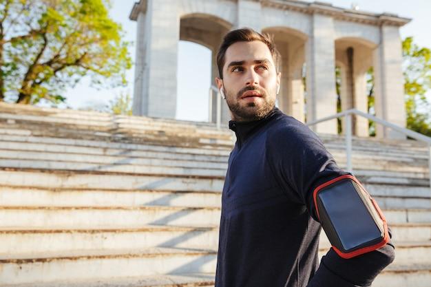 Afbeelding van een knappe jonge sterke sportman die buiten poseert op de locatie van het natuurpark met een mobiele telefoonhouder bij de hand, luister naar muziek.