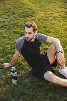 Afbeelding van een knappe jonge sterke sportman die buiten poseert op de locatie van het natuurpark, terwijl hij zit te luisteren naar muziek met oortelefoons.