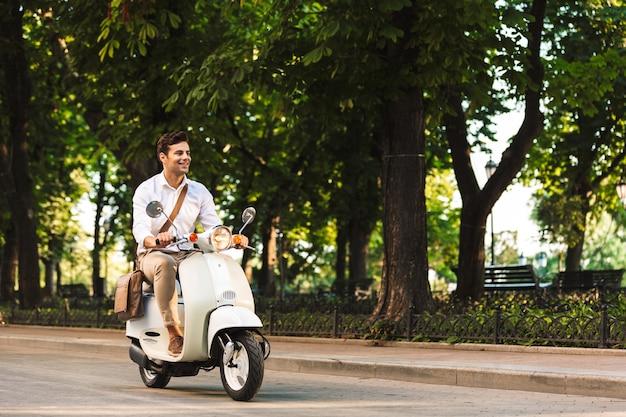 Afbeelding van een knappe jonge zakenman buiten lopen op scooter.