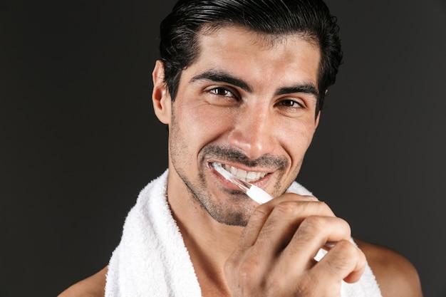 Afbeelding van een knappe jongeman poseren geïsoleerd zijn tanden poetsen.