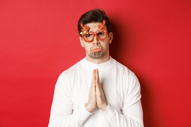Afbeelding van een knappe man met een kerstfeestbril, die om hulp smeekt of zich verontschuldigt, een gunst nodig heeft, staande op een rode achtergrond.