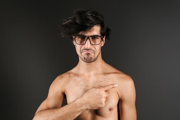 Afbeelding van een knappe naakte jongeman poseren geïsoleerd bril wijzend.