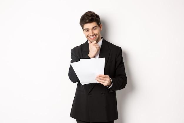 Afbeelding van een knappe zakenman in een zwart pak, die tevreden kijkt naar documenten, een rapport leest en glimlacht, staande tegen een witte achtergrond.