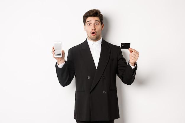 Afbeelding van een knappe zakenman in een zwart pak, die verbaasd kijkt en een creditcard toont met het scherm van de mobiele telefoon, staande tegen een witte achtergrond.
