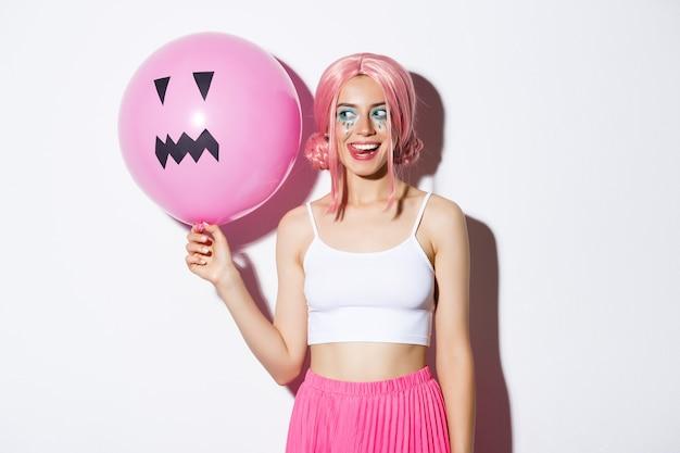 Afbeelding van een koket feestmeisje met lichte make-up, roze pruik dragend, ballon vasthoudend met jack-o'-lantern-gezicht, halloween vierend.
