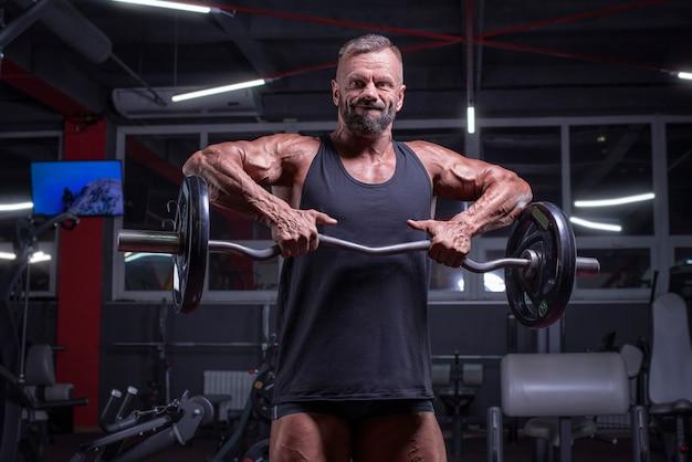 Afbeelding van een krachtige atleet die een halter opheft in een sportschool. schouder pompen. fitness en bodybuilding concept. gemengde media