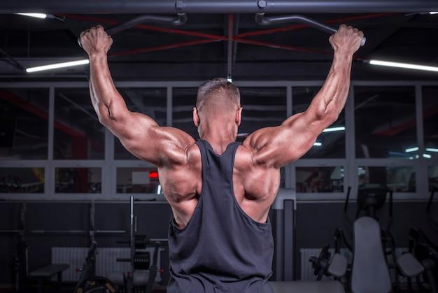 Afbeelding van een krachtige atleet die een pull-up doet in de sportschool. terug pompen. fitness en bodybuilding concept. gemengde media