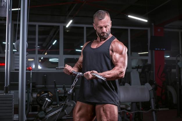 Afbeelding van een krachtige atleet die traint in een cross-over in de sportschool. biceps pompen. fitness en bodybuilding concept. gemengde media
