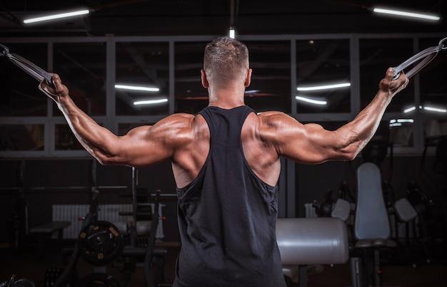 Afbeelding van een krachtige atleet die traint in een cross-over in de sportschool. fitness en bodybuilding concept. gemengde media
