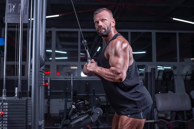 Afbeelding van een krachtige atleet die traint in een cross-over in de sportschool. triceps pompen. fitness en bodybuilding concept. gemengde media