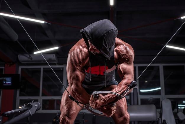Afbeelding van een krachtige atleet in een hoodie die traint in een cross-over in de sportschool. fitness en bodybuilding concept. gemengde media