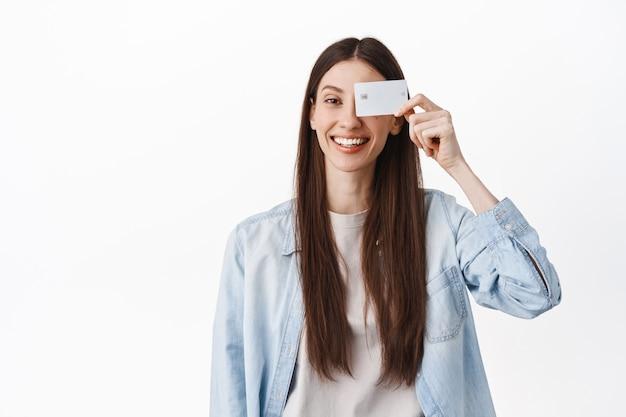Afbeelding van een lachend brunette meisje, met creditcard in de buurt van gezicht en positief kijkend, staande tegen een witte muur