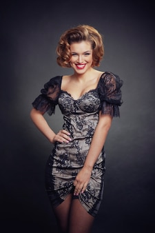 Afbeelding van een lachende vrouw met retro kapsel en make-up, in sexy zwarte jurk