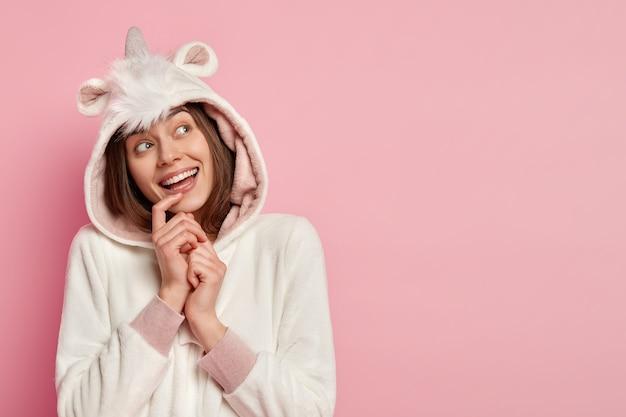 Afbeelding van een lachende vrouw met vrolijke dromerige uitdrukking, hoopt dat dromen uitkomen, lacht positief, draagt kigurumi-kostuum, poseert over roze muur, vrije ruimte voor uw promotie