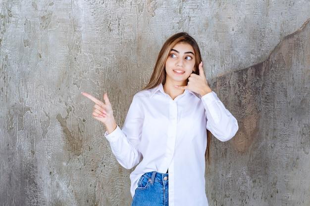 Afbeelding van een langharig jong meisje dat staat en wat tekens doet