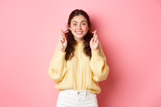 Afbeelding van een leuke vrolijke vrouw kruist haar vingers voor geluk en kijkt hoopvol naar de camera die een wens doet die over de roze muur staat