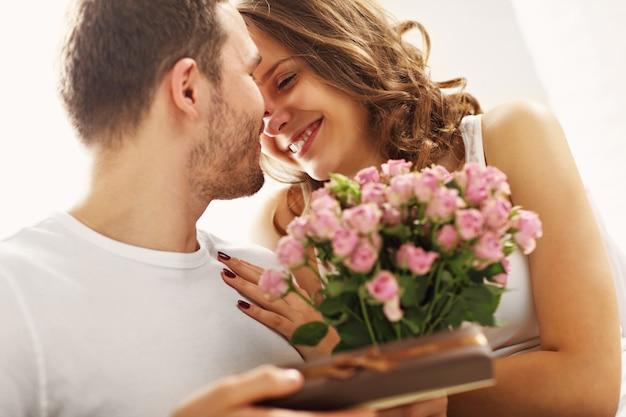 Afbeelding van een man die bloemen geeft en een cadeau geeft aan een vrouw in bed