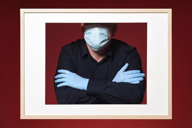 Afbeelding van een man handschoenen en masker armen gekruist op een rode achtergrond