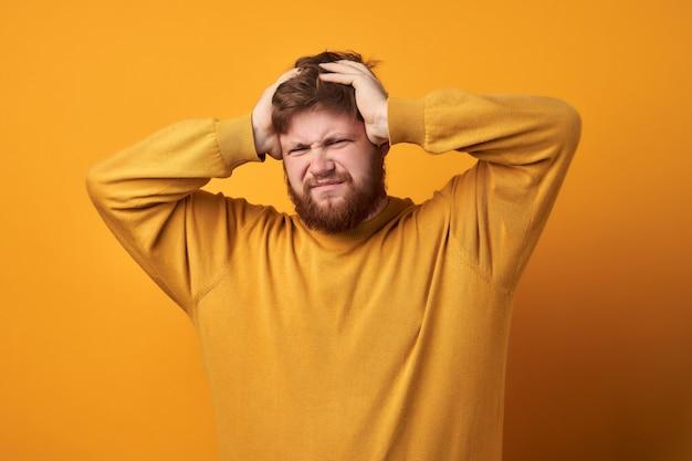 Afbeelding van een man in basiskleding, close-up van ongelukkig knappe man met baard haar met handen vast te houden