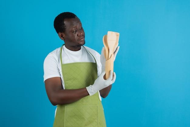 Afbeelding van een man in een groen schort die houten keukengerei vasthoudt tegen een blauwe muur