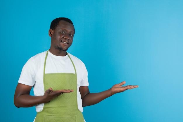 Afbeelding van een man in een groen schort met een geopende handpalm tegen een blauwe muur