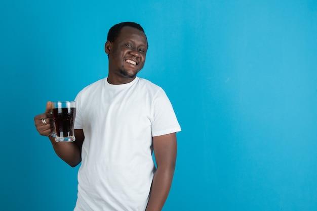 Afbeelding van een man in een wit t-shirt met een glazen mok wijn tegen een blauwe muur