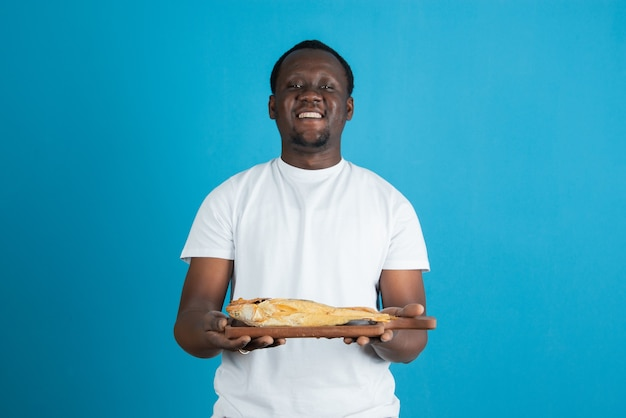 Afbeelding van een man in een wit t-shirt met een houten snijplank met gedroogde vis tegen een blauwe muur